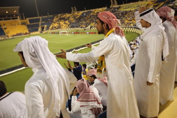 DOHA, QATAR - OCTOBER 23: Fans wearing traditional local dress react to play during the Gharafa vs. Kharaitiyat Qatar Stars League football match at Al Gharafa Stadium on October 23, 2011 in Doha, Qatar. Qatar will host the 2022 FIFA World Cup football c