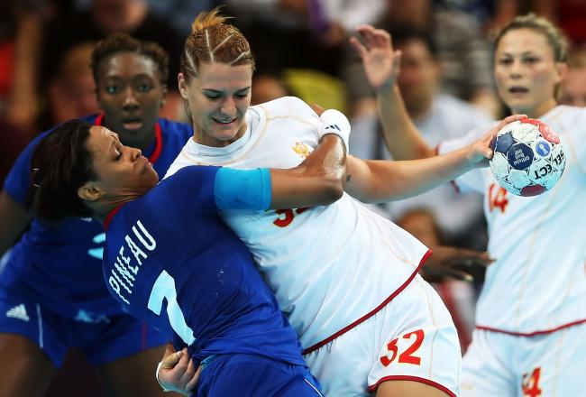 Montenegro's Katarina Bulatovic, center, wrestles France's Allison Pineau away before attempting a shot at goal.