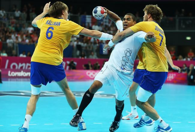 France's Daniel Narcisse, center, fights off the Swedish defense en route to a 23-22 win to keep the Olympic title.