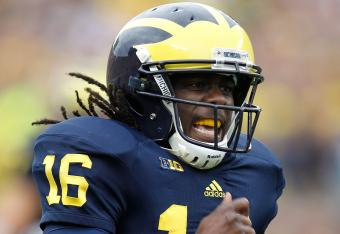 Denard Robinson takes a licking, but keeps on ticking.