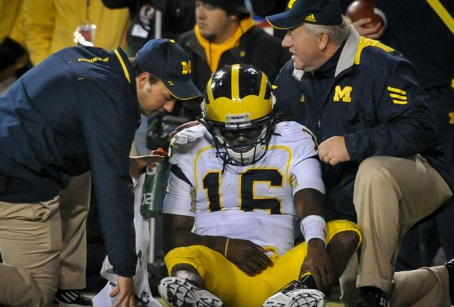 Coaches aide Denard Robinson after a tough fall that reportedly caused nerve problems in his right elbow.