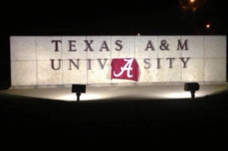 Fan Drapes Alabama Football Flag over Texas A&M University Sign