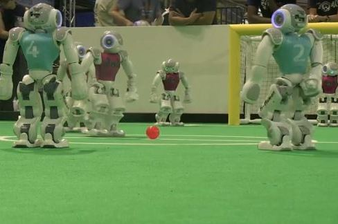 Computer-Controlled Robots at RoboCup Play with Goal of One Day Beating Humans
