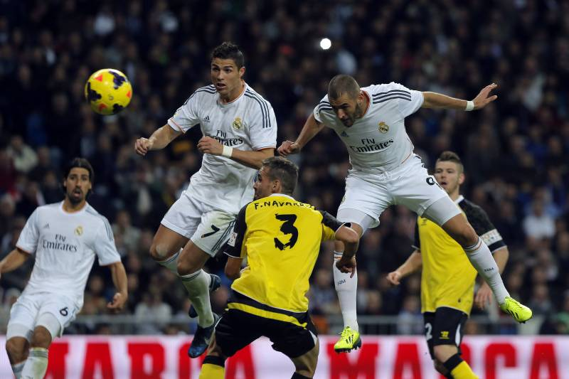 Real Madrid's Karim Benzema from France, right, scores his goal in between  players during