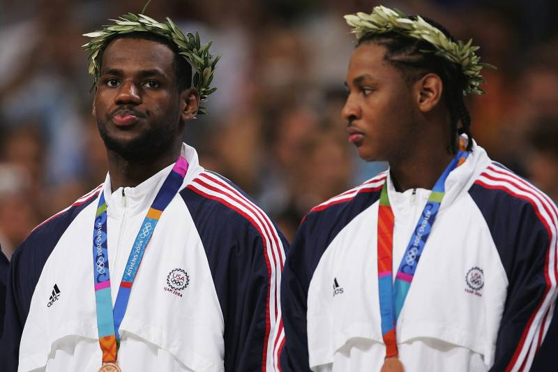 ATHENS - AUGUST 28:  (L-R) LeBron James #9 and Carmelo Anthony #8 of the United States receives the bronze medal for men's basketball during ceremonies on August 28, 2004 during the Athens 2004 Summer Olympic Games at the Indoor Hall of the Olympic Sports