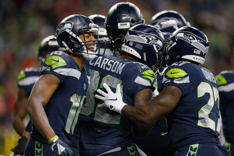 SEATTLE, WA - DECEMBER 23:  Chris Carson #32 of the Seattle Seahawks celebrates his touchdown on a one yard rush with teammates Mike Davis #27 and Tyler Lockett #16 (L) during the fourth quarter of the game against the Kansas City Chiefs at CenturyLink Fi