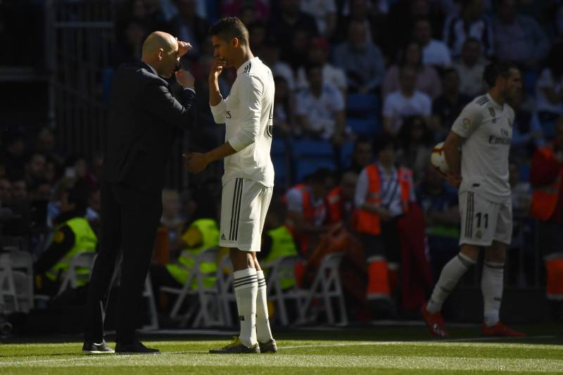 Real Madrid's French coach Zinedine Zidane talks to Real Madrid's French defender Raphael Varane during the Spanish league football match between Real Madrid CF and RC Celta de Vigo at the Santiago Bernabeu stadium in Madrid on March 16, 2019. (Photo by G