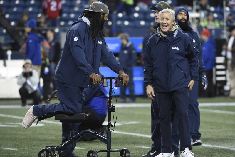 SEATTLE, WA - NOVEMBER 20: Cornerback Richard Sherman #25 of the Seattle Seahawks, out for the season with an Achilles injury, talks with Head coach Pete Carroll before the game at CenturyLink Field on November 20, 2017 in Seattle, Washington.  (Photo by