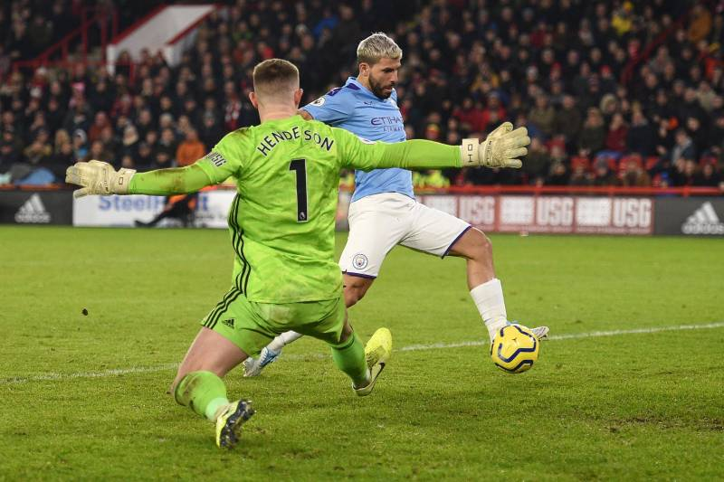 Manchester City's Argentinian striker Sergio Aguero (R) scores the opening goal past Sheffield United's English goalkeeper Dean Henderson during the English Premier League football match between Sheffield United and Manchester City at Bramall Lane in Shef