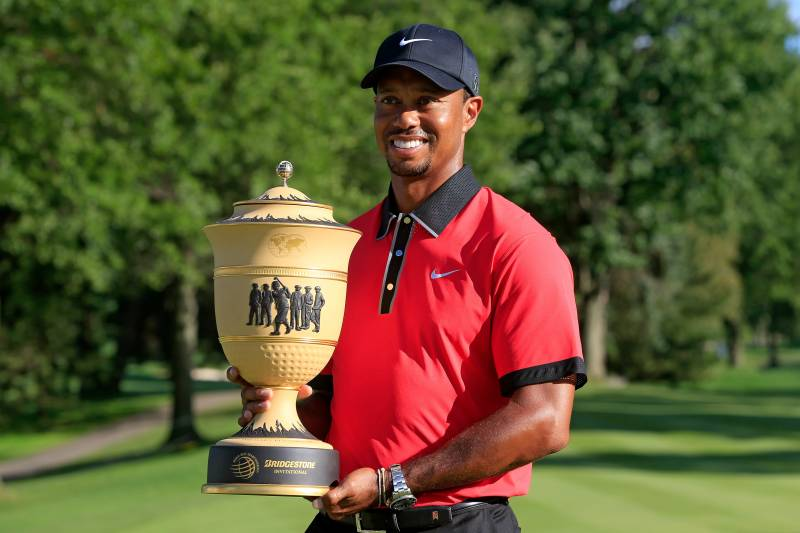 AKRON, OH - AUGUST 04: Tiger Woods holds the Gary Player Cup trophy after