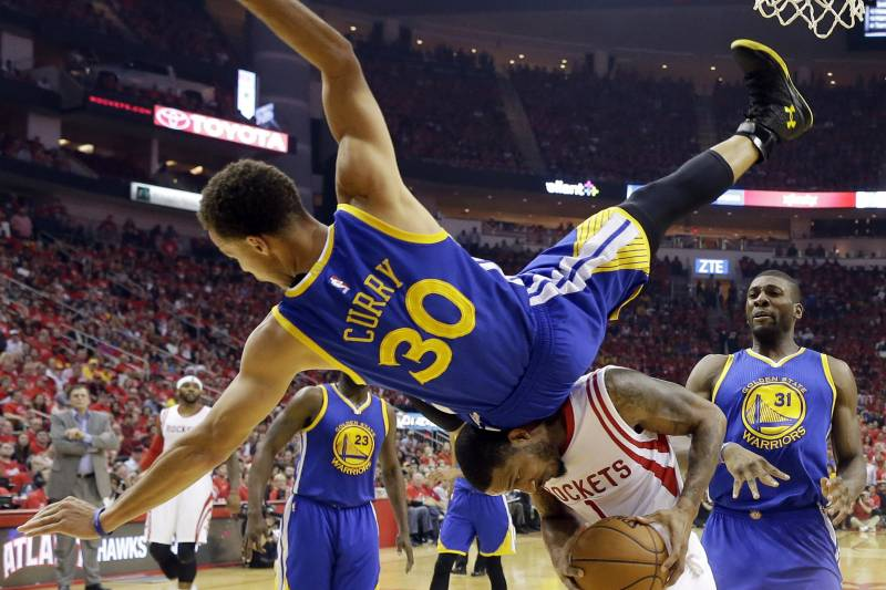 7394acdc881 Golden State Warriors guard Stephen Curry (30) topples over Houston Rockets  forward Trevor Ariza