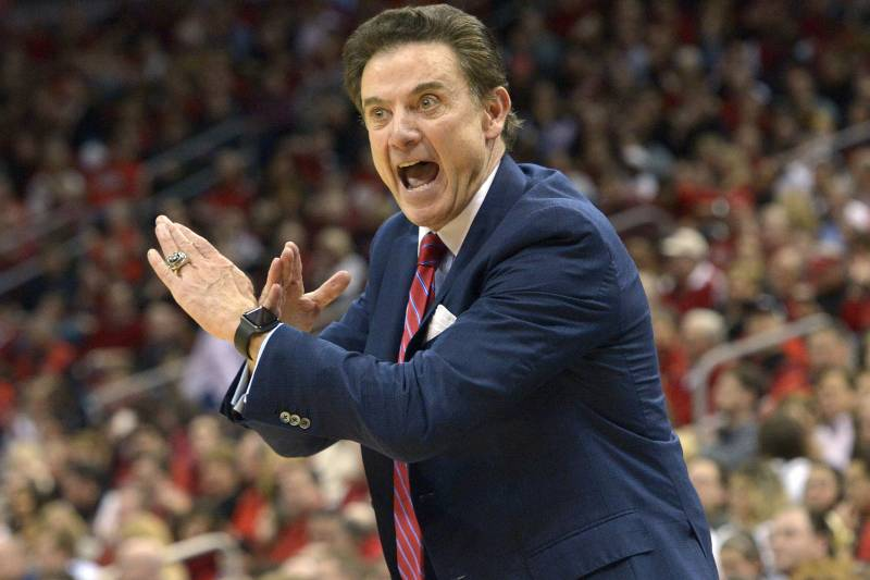 Louisville head coach Rick Pitino sends a play in to his team during the  first half
