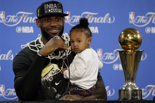 c753a843fd8f Cleveland Cavaliers  LeBron James answers questions as he holds his  daughter Zhuri during a post