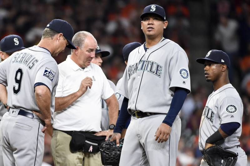 0a334a12a9 Seattle Mariners starting pitcher Felix Hernandez, second from right, is  checked out by manager