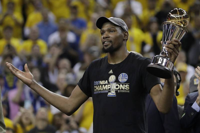 b26097fa5c3 Golden State Warriors forward Kevin Durant gestures as he holds the Bill  Russell NBA Finals Most