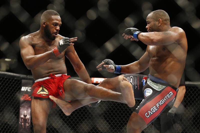 FILE - In this Jan. 3, 2015 file photo, Daniel Cormier, right, kicks Jon Jones during their light heavyweight title mixed martial arts bout at UFC 182, in Las Vegas. UFC is replacing its canceled Conor McGregor fight for another rematch, Jon Jones vs. Daniel Cormier for the light heavyweight title at UFC 200. UFC officials announced the replacement main event on Wednesday, April 27, 2016, several days after Jones beat Ovince Saint Preux by decision in his first fight since he had his title stripped in 2015.(AP Photo/John Locher, File)