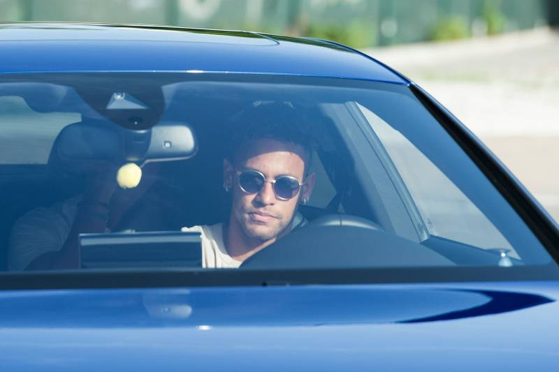TOPSHOT - Barcelona's Brazilian forward Neymar drives into the parkinglot to takes part in a training session at the Sports Center FC Barcelona Joan Gamper in Sant Joan Despi, near Barcelona on August 2, 2017 following rumour that Neymar is considering a move to French club PSG for which the club would have to shell out some 222 million euros, enough to trigger the 25-year-old's transfer release clause. / AFP PHOTO / Josep LAGO        (Photo credit should read JOSEP LAGO/AFP/Getty Images)