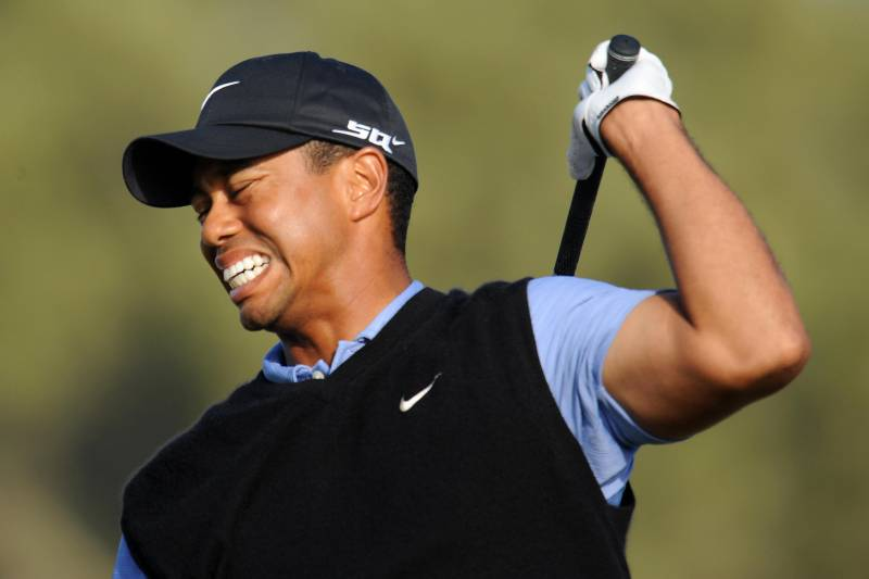Tiger Woods winces in pain as he follows thru on his shot from the 15th tee