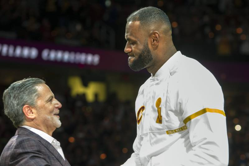 Cleveland Cavaliers\' LeBron James accepts his NBA championship ring from Cavaliers owner Dan Gilbert before a basketball game against the New York Knicks in Cleveland, Tuesday, Oct. 25, 2016. (AP Photo/Phil Long)
