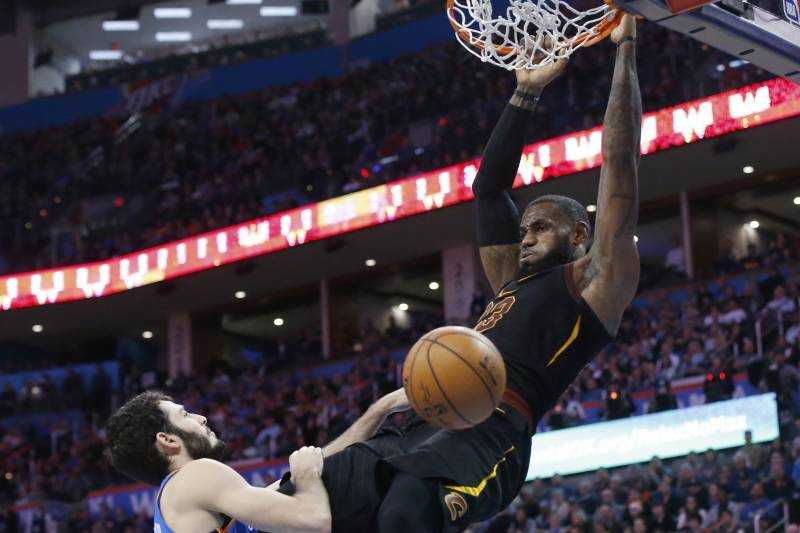 231a5e2f6210 Cleveland Cavaliers forward LeBron James hangs from the basket after  dunking in front of Oklahoma City