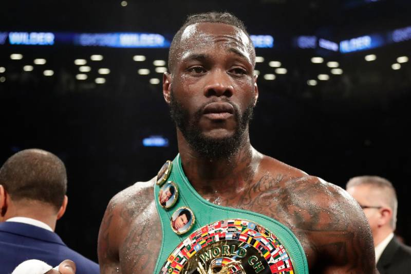 "FILE - In this March 3, 2018, file photo, Deontay Wilder poses for photographs after the WBC heavyweight champion defeated Luis Ortiz in New York. Wilder says he's ready to fight Anthony Joshua in a heavyweight unification bout, and is willing to travel overseas. Wilder cancelled a scheduled media conference call Tuesday, April 3, 2018, instead issuing a statement saying he's ""ready to come to the (United Kingdom) for my next fight."" (AP Photo/Frank Franklin II, File)"