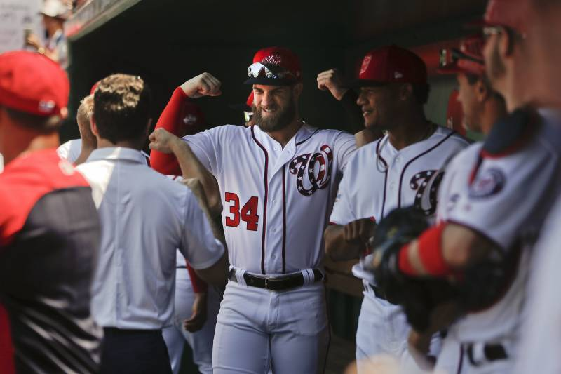 cc27ce3da Washington Nationals  Bryce Harper flexes his arms as he waits in the  dugout with his