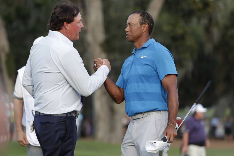 Phil Mickelson, left, shakes hands with Tiger Woods, after the first round of the Players Championship golf tournament, Thursday, May 10, 2018, in Ponte Vedra Beach, Fla. (AP Photo/Lynne Sladky)