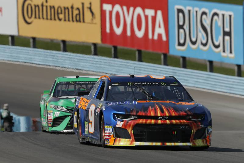 Chase Elliott (9) leads Kyle Busch (18) during a NASCAR Cup series auto race, Sunday, Aug. 5, 2018, in Watkins Glen, N.Y. (AP Photo/Julie Jacobson)