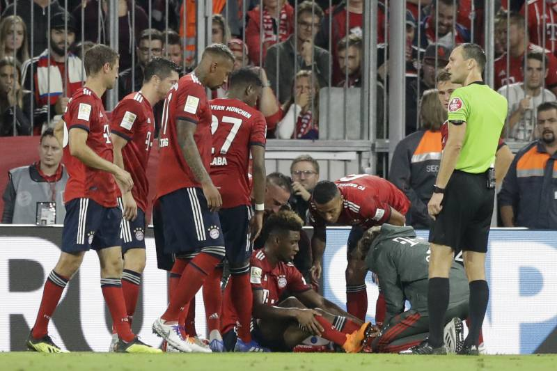 f1a37cea6 Bayern s Kingsley Coman sits injured on the ground during the German  Bundesliga soccer match between FC
