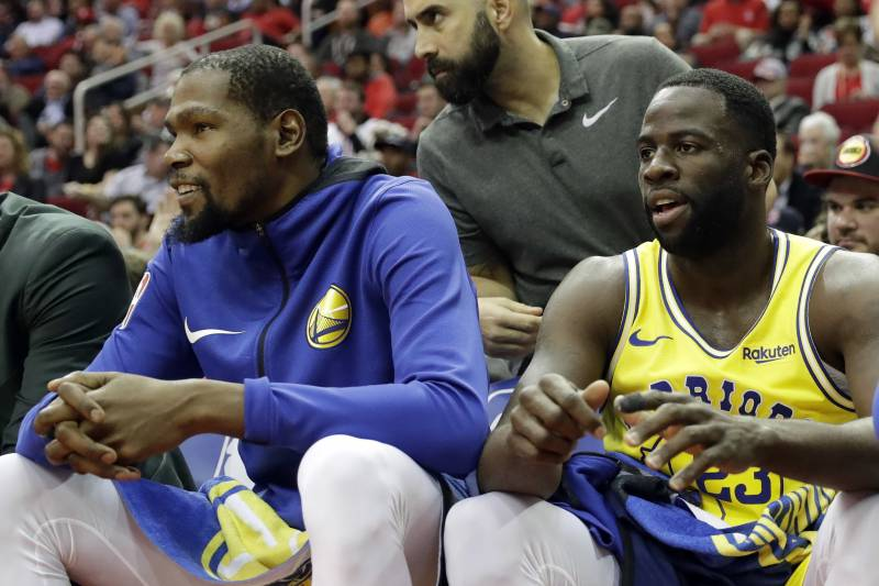 1ab1255d7dd Golden State Warriors' Kevin Durant, left, and Draymond Green sit on the  bench