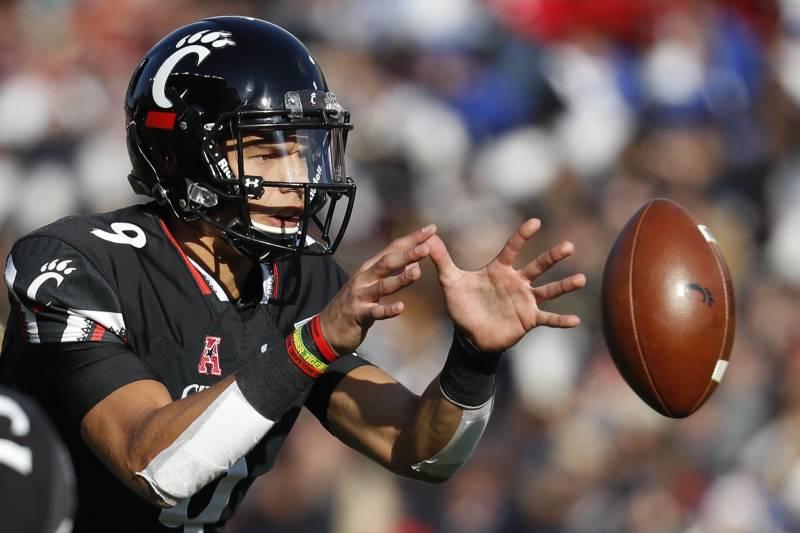 d3c08a5bf66780 Cincinnati quarterback Desmond Ridder takes the snap in the first half of  an NCAA college football