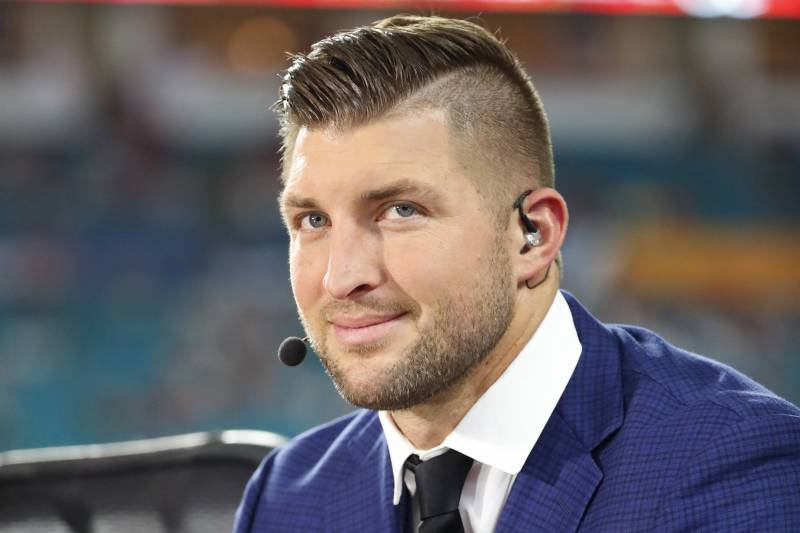 TV commentator Tim Tebow waits on the field, before the Orange Bowl NCAA college football game between Alabama and Oklahoma , Saturday, Dec. 29, 2018, in Miami Gardens, Fla. (AP Photo/Wilfredo Lee)