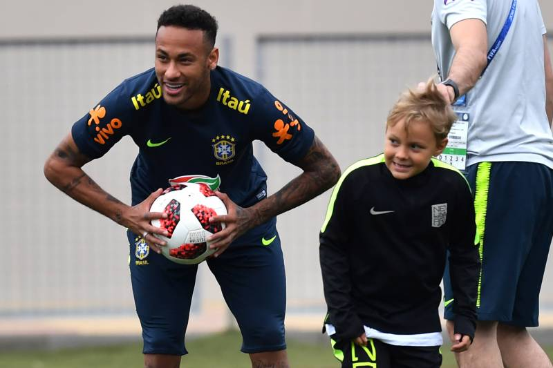 Brazil's forward Neymar (L) smiles past his son Davi Lucca during a training session at Yug Sport Stadium, in Sochi, on July 4, 2018, during the Russia 2018 World Cup football tournament. (Photo by NELSON ALMEIDA / AFP)        (Photo credit should read NELSON ALMEIDA/AFP/Getty Images)