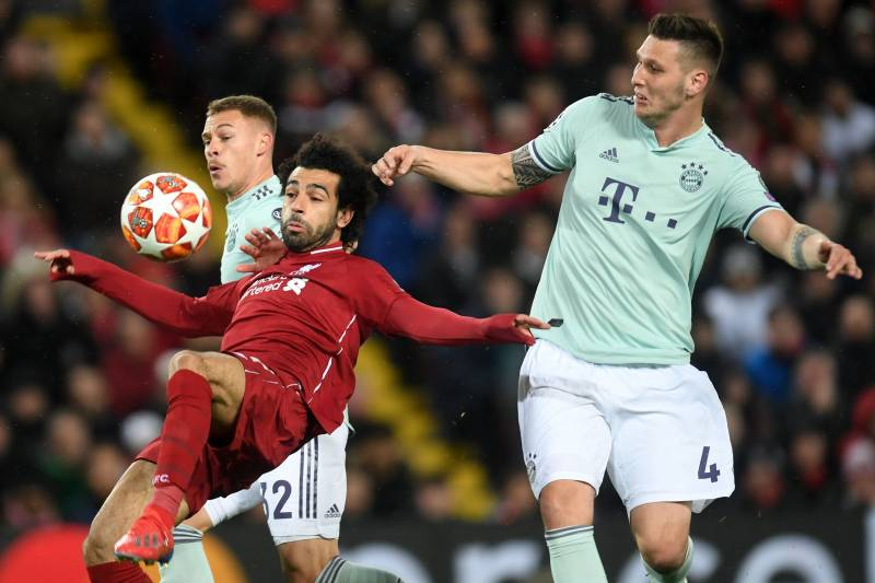 06db3cbcc Liverpool s Egyptian midfielder Mohamed Salah (C) controls the ball under  pressure from Bayern Munich s