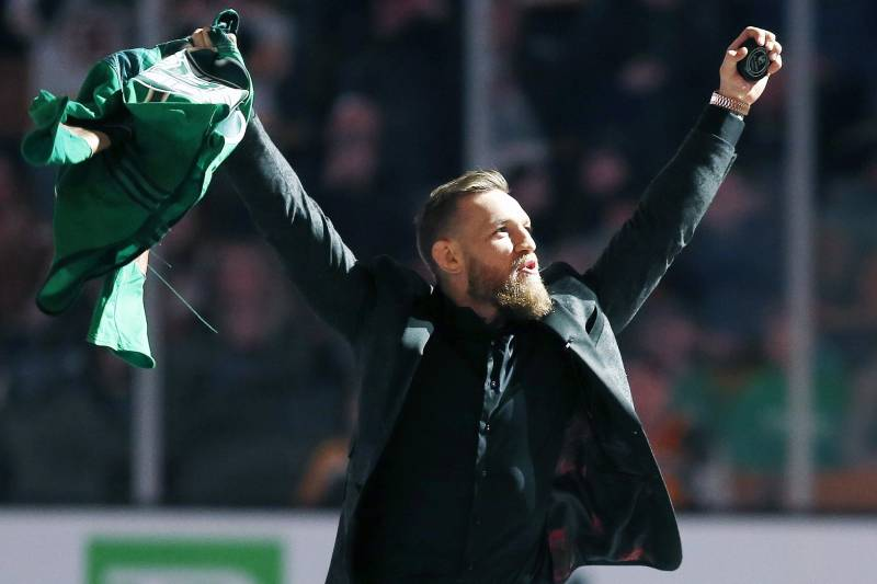 Mixed martial arts fighter and boxer Conor McGregor salutes the crowd before making the ceremonial puck drop at an NHL hockey game between the Boston Bruins and the Columbus Blue Jackets in Boston, Saturday, March 16, 2019. (AP Photo/Michael Dwyer)