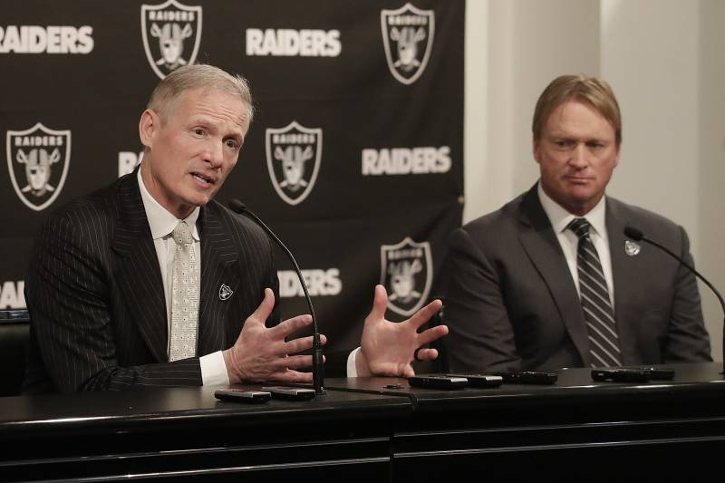 FILE - In this Monday, Dec. 31, 2018, file photo, Mike Mayock, left, speaks as Oakland Raiders head coach Jon Gruden listens at a news conference announcing Mayock as the general manager at the team's headquarters in Oakland, Calif. Mayock knows he will be highly scrutinized with three first-round picks thanks to Gruden's much-criticized trades.