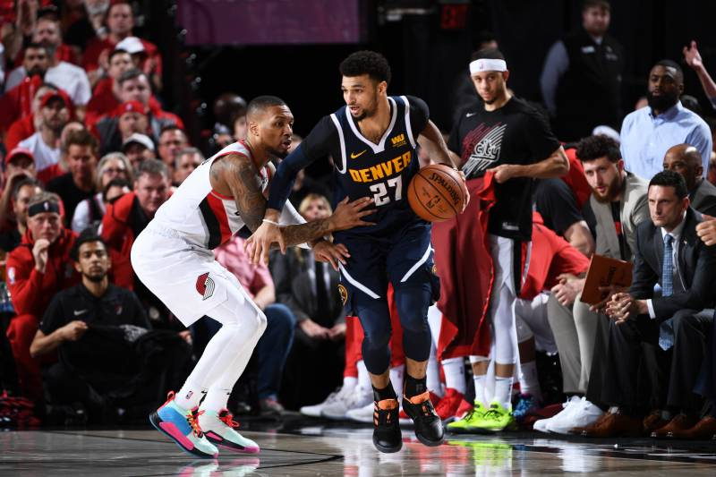 PORTLAND, OR - MAY 5: Jamal Murray #27 of the Denver Nuggets handles the ball against Damian Lillard #0 of the Portland Trail Blazers during Game Four of the Western Conference Semifinals on May 5, 2019 at the Moda Center Arena in Portland, Oregon. NOTE TO USER: User expressly acknowledges and agrees that, by downloading and or using this photograph, user is consenting to the terms and conditions of the Getty Images License Agreement.