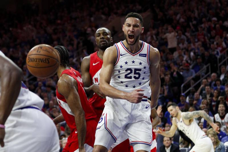 Philadelphia 76ers' Ben Simmons, right, reacts after a dunk as Toronto Raptors' Serge Ibaka watches during the first half of Game 6 of a second-round NBA basketball playoff series Thursday, May 9, 2019, in Philadelphia. (AP Photo/Chris Szagola)