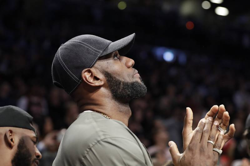 LeBron James applauds as he watches on a giant overhead video screen as a member of the military is honored during a timeout in the first half of an NBA basketball game between the Brooklyn Nets and the Miami Heat, Wednesday, April 10, 2019, in New York. James and other NBA stars, including Houston Rockets Chris Paul, left, turned out to watch final game of Miami Heat guard Dwyane Wade's NBA career.
