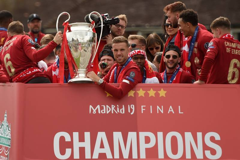 5eb105542 Liverpool's English midfielder Jordan Henderson (C) holds the European  Champion Clubs' Cup trophy