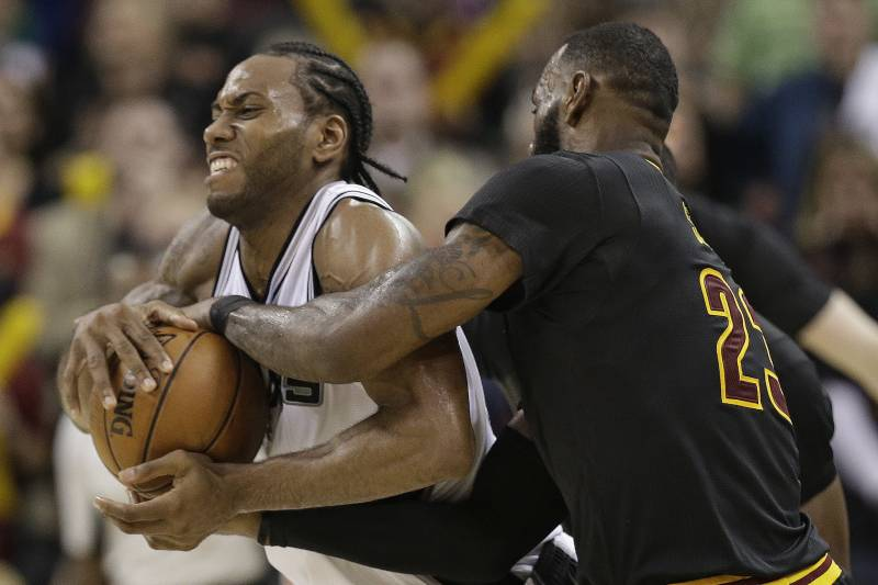 San Antonio Spurs' Kawhi Leonard, left, and Cleveland Cavaliers' LeBron James brab the ball which resulted in a jump ball in overtime in an NBA basketball game, Saturday, Jan. 21, 2017, in Cleveland. (AP Photo/Tony Dejak)