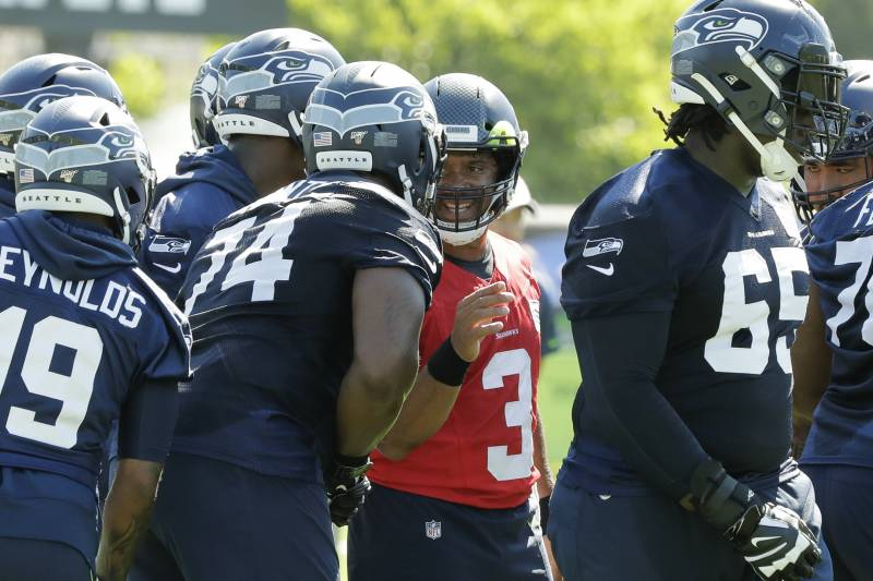 Seattle Seahawks quarterback Russell Wilson (3) talks with offensive tackle George Fant (74) during NFL football training camp, Thursday, July 25, 2019, in Renton, Wash. (AP Photo/Ted S. Warren)
