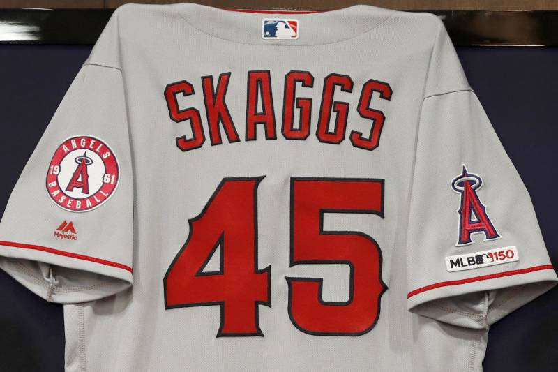 The jersey of the late Tyler Skaggs hangs on the wall during a news conference with team management and ownership before a baseball game against the Texas Rangers in Arlington, Texas, Tuesday, July 2, 2019. Skaggs passed away on Monday in Southlake, Texas. (AP Photo/Tony Gutierrez)
