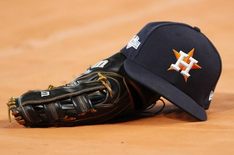 HOUSTON, TX - OCTOBER 19:  A Houston Astros hat and glove are seen on the field before Game Six of the League Championship Series against the New York Yankees at Minute Maid Park on October 19, 2019 in Houston, Texas.  (Photo by Tim Warner/Getty Images)