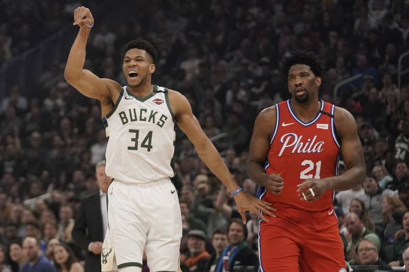 Milwaukee Bucks' Giannis Antetokounmpo reacts to his shot in front of Philadelphia 76ers' Joel Embiid during the first half of an NBA basketball game Saturday, Feb. 22, 2020, in Milwaukee. (AP Photo/Morry Gash)