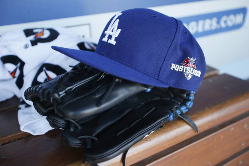 A Los Angeles Dodgers hat with a postseason logo on it is seen above a glove on the bench during rehearsals for the upcoming NLDS baseball playoff series against the New York Mets, Tuesday October 6, 2015, in Los Angeles. Their best of the five NLDS playoff series begins on Friday 9 October at Dodger Stadium. (Photo AP / Danny Moloshok)