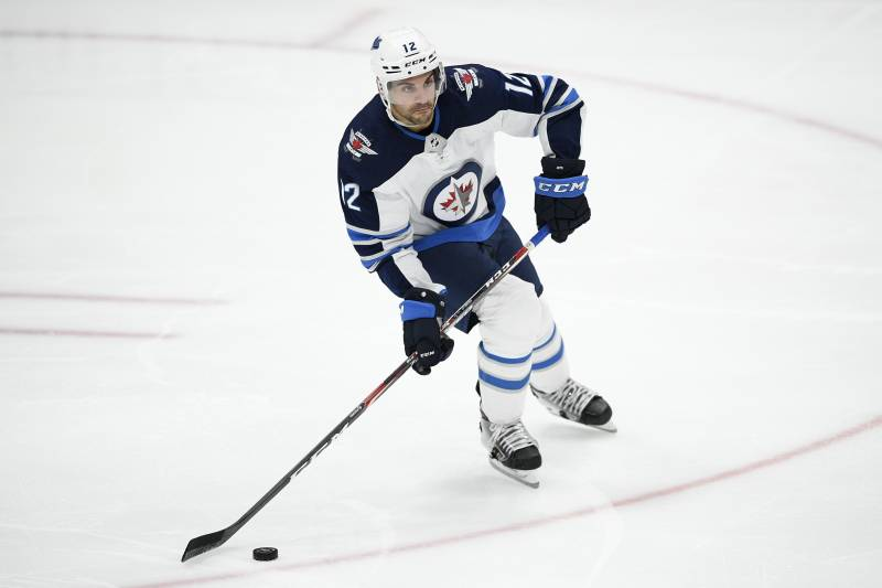 Winnipeg Jets defenseman Dylan DeMelo (12) skates with the puck during the third period of an NHL hockey game against the Washington Capitals, Tuesday, Feb. 25, 2020, in Washington. The Capitals won 4-3 in shootout. (AP Photo/Nick Wass)