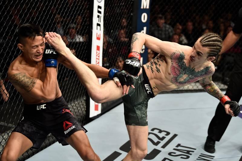 Sean O'Malley (right) kicks Andre Soukhamthath